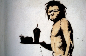 A Paleolithic Man holding a tray of fast food - Not Paleo Diet friendly