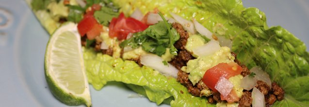 A romaine lettuce leaf stuffed with ground beef, guacamole, and a blend of tomatoes, onions and cilantro